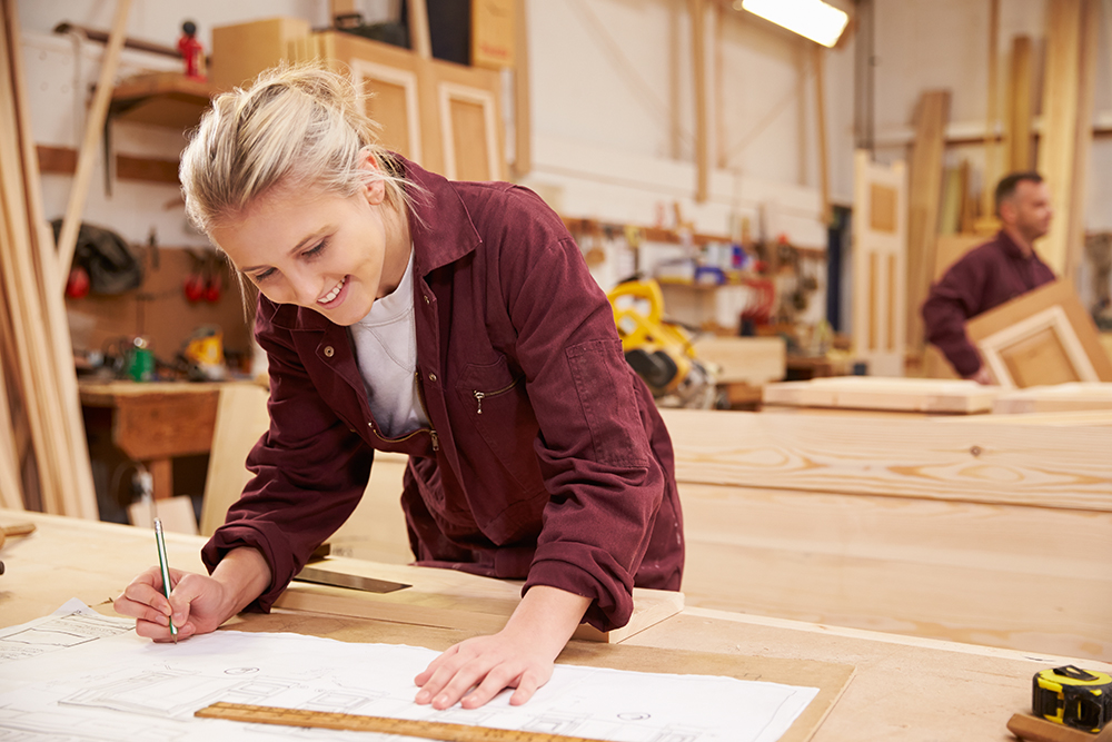 1-female-apprentice-working-with-plans-in-carpentry-P2DQC94